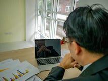 Το επιχειρησιακό άτομο παίρνει έναν σοβαρό και εξετάζει το lap-top στοκ εικόνες