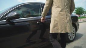 Το επιχειρησιακό άτομο που έρχεται στο αυτοκίνητο και ανοίγει την πόρτα Ο τύπος κάθεται μέσα στο αυτοκίνητο απόθεμα βίντεο