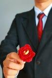 Το επιχειρησιακό άτομο στην παρουσίαση κοστουμιών αυξήθηκε και το γαμήλιο δαχτυλίδι Στοκ φωτογραφία με δικαίωμα ελεύθερης χρήσης