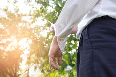 Το επιχειρησιακό άτομο στο κοστούμι και ένα άσπρο πουκάμισο κυλά επάνω τα μανίκια του στο ν στοκ εικόνες με δικαίωμα ελεύθερης χρήσης