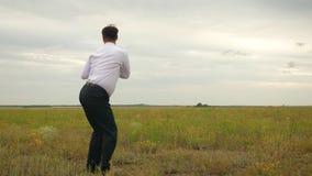 Το επιχειρησιακό άτομο στο επιχειρησιακό κοστούμι με το χαρτοφύλακα των εγγράφων στο χέρι του χορεύει και χαίρεται για την τέλεια απόθεμα βίντεο