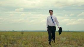 Το επιχειρησιακό άτομο στο επιχειρησιακό κοστούμι περπατά πέρα από τον τομέα με το χαρτοφύλακα των εγγράφων στο χέρι του Γεωπόνος φιλμ μικρού μήκους