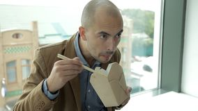 Το επιχειρησιακό άτομο στο πανοραμικό παράθυρο του εμπορικού κέντρου τρώει τα κινεζικά νουντλς Εργασία, μεσημεριανό γεύμα απόθεμα βίντεο
