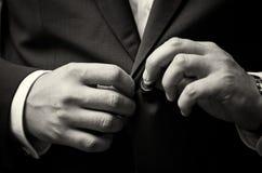 Το επιχειρησιακό άτομο τακτοποιεί το κουμπί του κοστουμιού του, κάνει μια τακτοποιημένη εικόνα Στοκ Εικόνες