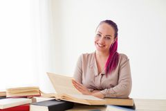 Το επιχειρησιακό κορίτσι κάθεται στο γραφείο για τους φακέλλους βιβλίων του εγγράφου Στοκ Φωτογραφία