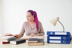 Το επιχειρησιακό κορίτσι κάθεται στο γραφείο για τους φακέλλους βιβλίων του εγγράφου Στοκ Φωτογραφίες