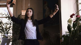 Το επιχειρησιακό κορίτσι κάνει το selfi το εικοστό τηλέφωνο συγχρόνως Ένας χαριτωμένος μακρυμάλλης σπουδαστής brunette φιλμ μικρού μήκους