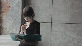 Το επιχειρησιακό κορίτσι με τον πράσινο φάκελλο διαθέσιμο γράφει απόθεμα βίντεο