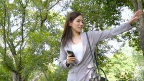Το επιχειρησιακό κορίτσι χρησιμοποιεί το smartphone και αυξάνει το χέρι για να καλέσει άλλο φίλο ανθρώπων στο πάρκο κήπων σε σε α φιλμ μικρού μήκους