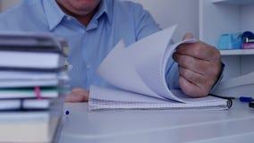 Το επιχειρησιακό πρόσωπο κοιτάζει βιαστικά τις σελίδες καταλόγων λογιστικής που ψάχνουν τις οικονομικές πληροφορίες φιλμ μικρού μήκους