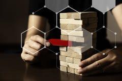 Το επιχειρησιακό χέρι προσπαθεί να επιλέξει τον ξύλινο φραγμό κόκκινου χρώματος στοκ εικόνες με δικαίωμα ελεύθερης χρήσης