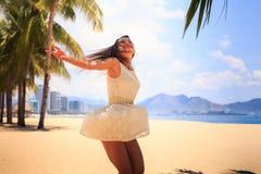 το λεπτό κορίτσι κατά την άσπρη άποψη πίσω πλευρών θέτει με τα χέρια επάνω στην παραλία Στοκ Εικόνες