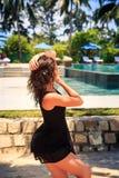 το λεπτό κορίτσι μαύρο σε ξυπόλυτο θέτει ενάντια στη λίμνη και τις ομπρέλες Στοκ Εικόνες