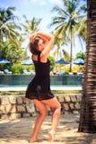 το λεπτό κορίτσι μαύρο σε ξυπόλυτο θέτει ενάντια στη λίμνη και τις ομπρέλες Στοκ Εικόνα
