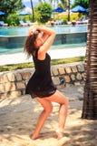 το λεπτό κορίτσι μαύρο σε ξυπόλυτο θέτει ενάντια στη λίμνη και τις ομπρέλες Στοκ εικόνα με δικαίωμα ελεύθερης χρήσης