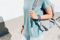 Το λεπτό κορίτσι σε μια μπλούζα με ένα σακίδιο πλάτης πηγαίνει υπαίθρια στο summe Στοκ Εικόνες