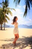 το λεπτό κορίτσι στο άσπρο φόρεμα θέτει με τα χέρια κατά μέρος στην παραλία Στοκ Εικόνα