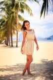 το λεπτό κορίτσι στο άσπρο φόρεμα θέτει χωρίς παπούτσια ενάντια στη σειρά των φοινικών Στοκ φωτογραφία με δικαίωμα ελεύθερης χρήσης