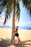 το λεπτό κορίτσι στο μαύρο φόρεμα δαντελλών αγγίζει χωρίς παπούτσια το φοίνικα στην παραλία Στοκ Εικόνες