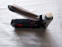 το εργαλείο για τις οικοδομές, ένα stsepler του μαύρου χρώματος συνδέει τα αντικείμενα με τα άσπρα υποστηρίγματα μετάλλων λαβών, στοκ φωτογραφία με δικαίωμα ελεύθερης χρήσης