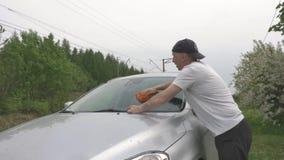Το εργατικό άτομο στην μπλούζα πλένει το σύγχρονο γκρίζο παράθυρο αυτοκινήτων απόθεμα βίντεο