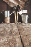 Το εργαλείο κήπων, φτυάρι, τσουγκράνα, πότισμα μπορεί, κάδος, να τοποθετήσει σε σάκκο σε έναν ξύλινο Στοκ φωτογραφίες με δικαίωμα ελεύθερης χρήσης