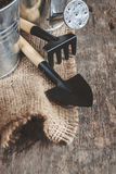 Το εργαλείο κήπων, φτυάρι, τσουγκράνα, πότισμα μπορεί, κάδος, να τοποθετήσει σε σάκκο σε έναν ξύλινο Στοκ Φωτογραφία