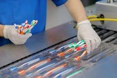 Το εργοστάσιο παράγει και συσκευάζει τις οδοντόβουρτσες των διαφορετικών χρωμάτων στοκ εικόνες