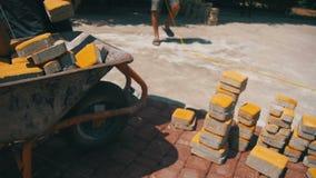 Το εργοτάξιο οικοδομής, ο εργάτης οικοδομών ξεφορτώνει την πέτρινη επίστρωση από wheelbarrow κίνηση αργή απόθεμα βίντεο