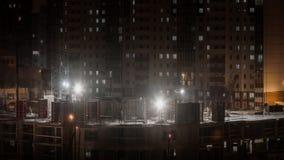 Το εργοτάξιο οικοδομής στην πόλη, κατασκευαστές που εργάζεται στο άσχημο καιρό ρυθμίζει τη χιονίζοντας χειμερινή νύχτα φιλμ μικρού μήκους