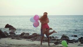 Το ερωτευμένο τρέξιμο ζεύγους που κρατά ο ένας στον άλλο τα πολύχρωμα μπαλόνια που αγκαλιάζουν την περιστροφή έχει γύρω την απόλα φιλμ μικρού μήκους