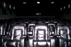 Το εσωτερικό μιας αίθουσας κινηματογράφων με τα μαύρα καθίσματα δέρματος Η ταινία δεν παρουσιάζει και κανένας άνθρωπος στοκ φωτογραφία