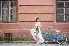 Το ευγενές κορίτσι στο ελαφρύ φόρεμα με τα peonies κοίταξε κάτω στοκ εικόνα