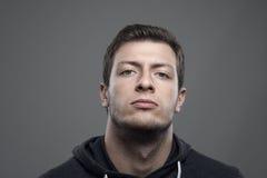 Το ευμετάβλητο πορτρέτο του υπερήφανου νεαρού άνδρα με το κεφάλι έκλινε την πίσω εξέταση το camer Στοκ Φωτογραφία