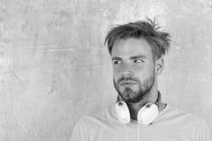 Το ευρωπαϊκό άτομο έχει το χρόνο διασκέδασης Αμερικανικός όμορφος γενειοφόρος τύπος με τα ακουστικά Εύθυμα τραγούδια ακούσματος ε στοκ φωτογραφίες