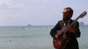 το ευρωπαϊκό άτομο παίζει την κιθάρα ενάντια στη θάλασσα με την εστίαση στις βάρκες απόθεμα βίντεο