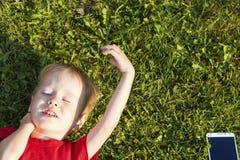 Το ευρωπαϊκό αγόρι παιδιών εναπόκειται στις προσοχές του ιδιαίτερες στη χλόη και τα υπόλοιπα Η έννοια της εκπαίδευσης και της εξά στοκ εικόνα με δικαίωμα ελεύθερης χρήσης
