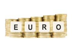 Το ΕΥΡΩ λέξης (ευρωπαϊκό νόμισμα) στους χρυσούς σωρούς νομισμάτων απομόνωσε το λευκό Στοκ Εικόνες