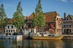 Το ευρύ κανάλι με τα σπίτια τούβλου, βάρκες έδεσε στην τράπεζά του που απεικονίστηκε στο νερό και το μπλε ουρανό του ηλιοβασιλέμα Στοκ Εικόνες