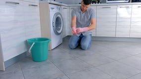 Το ευτυχές άτομο βάζει στα λαστιχένια γάντια για να καθαρίσει την κουζίνα φιλμ μικρού μήκους