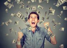 Το ευτυχές άτομο γιορτάζει την επιτυχία κάτω από τη βροχή χρημάτων Στοκ Φωτογραφία