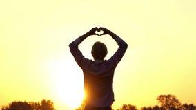 Το ευτυχές άτομο κρατά τα χέρια κατά μέρος σε μια τράπεζα λιμνών στο ηλιοβασίλεμα απόθεμα βίντεο