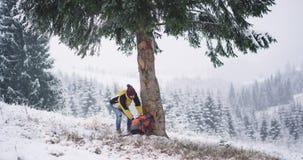 Το ευτυχές άτομο τουριστών έφθασε στην καταπληκτική θέση στο βουνό που βρήκε ένα μεγάλο χιονώδες δέντρο και σταμάτησε για να θαυμ απόθεμα βίντεο
