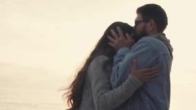Το ευτυχές άτομο φιλά τη φίλη του στο μέτωπο, που περπατά στη φύση, ενάντια στον ήλιο απόθεμα βίντεο