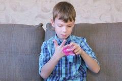 Το ευτυχές αγόρι βάζει ρόδινο slime στη συνεδρίαση χεριών του στο λεωφορείο και το παιχνίδι στοκ εικόνες