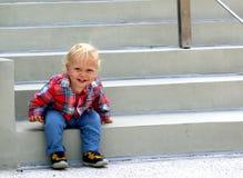 Το ευτυχές αγόρι σηκώνεται από τα σκαλοπάτια Στοκ Εικόνα