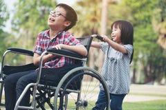 Το ευτυχές αγόρι στην αναπηρική καρέκλα με το κορίτσι δοκιμάζει την κίνηση μια αναπηρική καρέκλα της Στοκ Φωτογραφίες