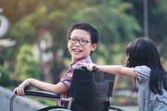 Το ευτυχές αγόρι στην αναπηρική καρέκλα με το κορίτσι δοκιμάζει την κίνηση μια αναπηρική καρέκλα της Στοκ Εικόνα
