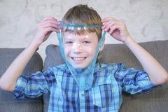 Το ευτυχές αγόρι τεντώνει μια μπλε slime συνεδρίαση στο λεωφορείο και το παιχνίδι Κοίταγμα μέσω slime στοκ εικόνα με δικαίωμα ελεύθερης χρήσης