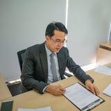 Το ευτυχές ασιατικό επιχειρησιακό άτομο εξετάζει το αρχείο εγγράφων του στο γραφείο στοκ φωτογραφίες με δικαίωμα ελεύθερης χρήσης